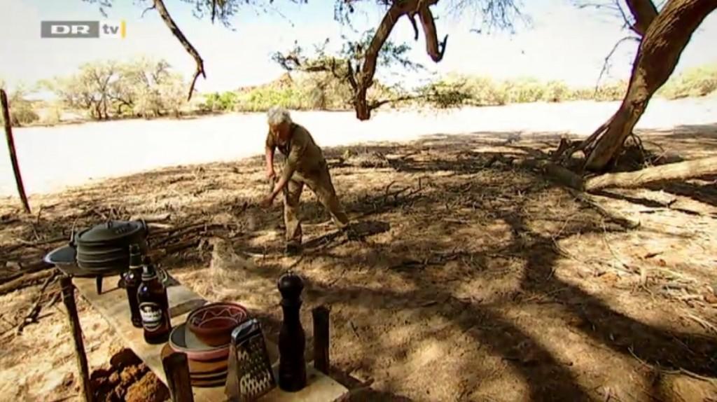 """""""Er det ikke lidt for svanset, det der?"""", spørger Nikolaj Kirk. Jørgen Skouboe fejer i lejren i Afrika. Billede fra dr.dk/tv."""